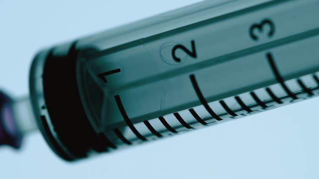 a syringe filling injection medication on a blue background. macro - syringe stock videos & royalty-free footage