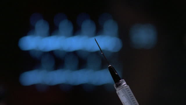 a syringe squirts serum into the air. - operating gown stock videos & royalty-free footage