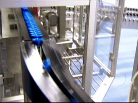 Syringe tubes moving down bottle distribution slide onto conveyor belt at pharmaceutical factory