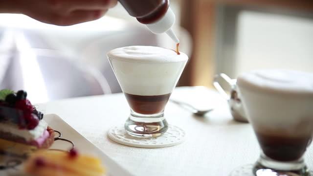 vídeos de stock, filmes e b-roll de syrup design on latte - xarope