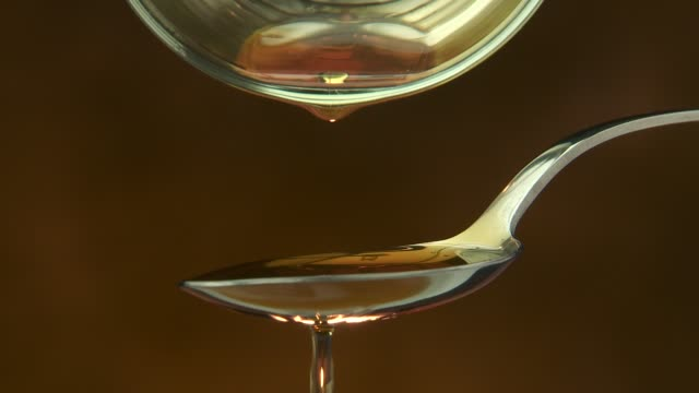 syrup or oil pour drips into spoon