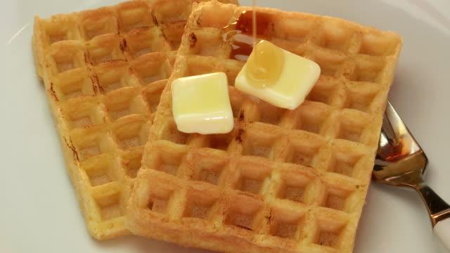 vídeos y material grabado en eventos de stock de syrup poured over waffles and melting butter - waffles