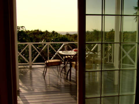 stockvideo's en b-roll-footage met ms,  table and chairs on terrace overlooking lush foliage,  harbour island,  bahamas - plate met stilstaande achtergrond
