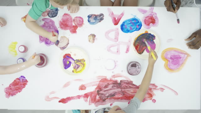 Table Covered in Paintings from Children