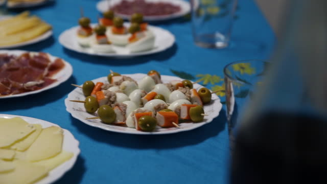 table full of starters, with serrano ham, cheese, asparagus, chorizo and eggs skewers. - chorizo stock videos & royalty-free footage