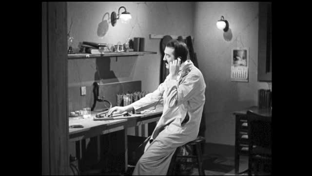 vídeos y material grabado en eventos de stock de table full of various tools and wires; man in white lab coat picking up tool and sitting in front of workbench, listens to something on the telephone... - 1940 1949