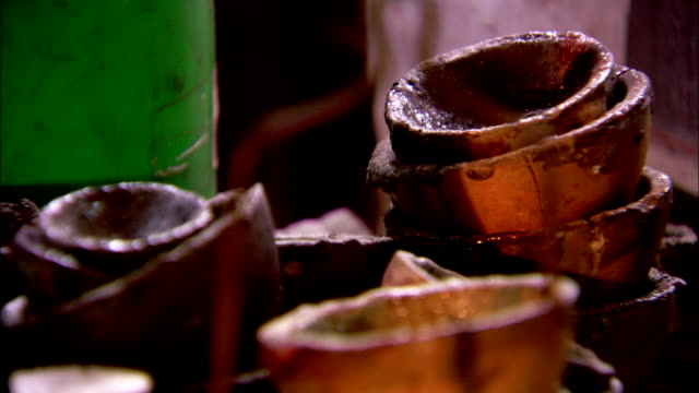 a table holds a variety of rustic pots. available in hd. - 陶器点の映像素材/bロール