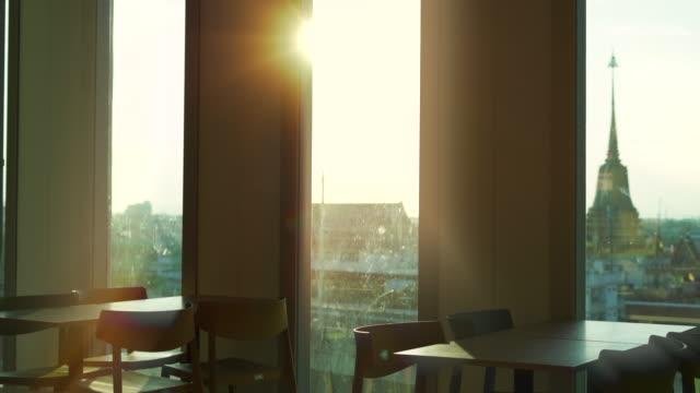 vidéos et rushes de table dans le bâtiment avec le soleil sur le camion de fenêtre tiré - chaise de bureau
