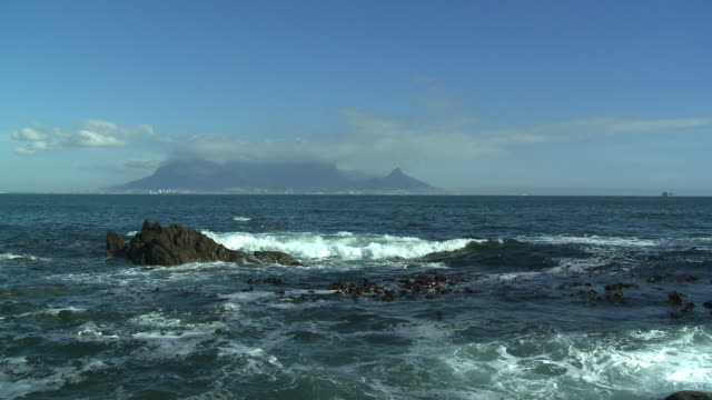 ws table mountain across table bay with waves breaking in foreground, cape town, western cape, south africa - テーブルマウンテン国立公園点の映像素材/bロール