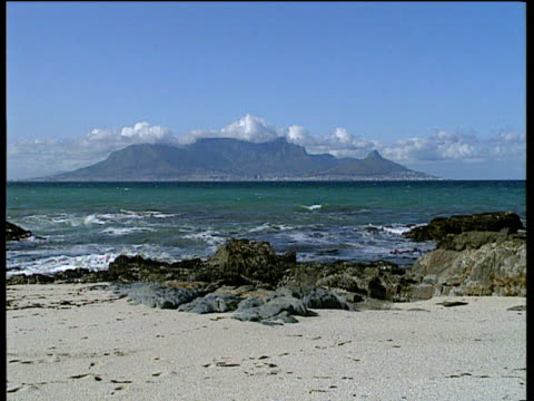 Table Mountain with cloud resting on top Cape Town nestled below sea in foreground