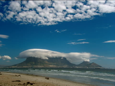 Table Mountain with layer of cloud resting on top waves lap onto sandy beach in foreground