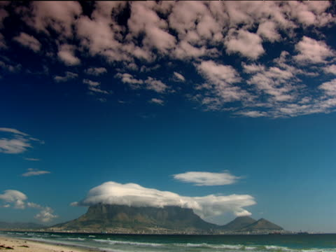 Table Mountain with layer of cloud resting on top waves lap onto beach in foreground