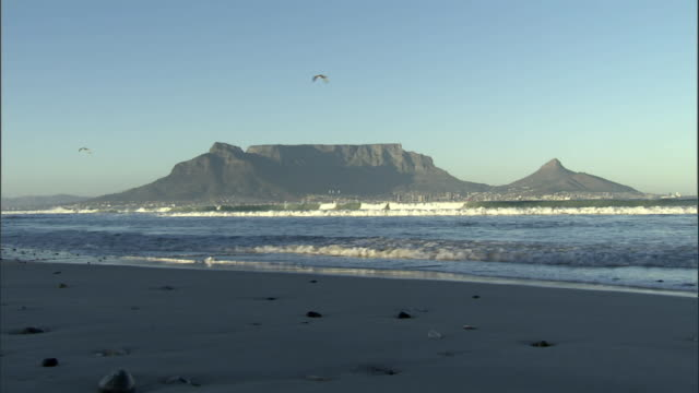 ws table mountain with waves hitting shore in foreground/ cape town, south africa - 南ア テーブルマウンテン点の映像素材/bロール