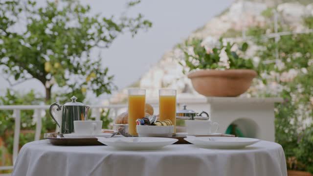 vidéos et rushes de slo mo table préparée pour le petit déjeuner sur un balcon d'une villa à positano - station de vacances
