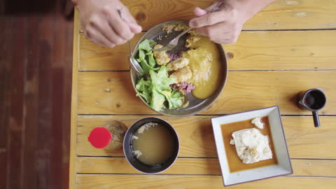 table top view of man eating tempeh curry with rice and cold tofu. - japanese food stock videos & royalty-free footage