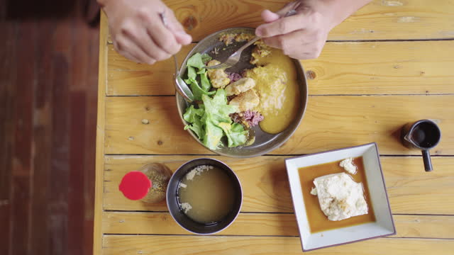 table top view of man eating tempeh curry with rice and cold tofu. - table top view stock videos & royalty-free footage