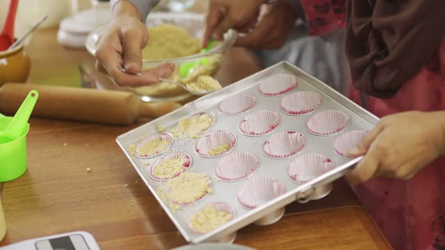table top view ramadan malaysian malay adult offspring helping mother baking in kitchen preparing family at home celebrating hari raya - sweet food stock videos & royalty-free footage