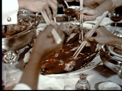 vidéos et rushes de 1957 montage table w/ chinese food + peking duck. chinese woman shows tourist man how to eat w/ chopsticks / singapore / audio - culture chinoise