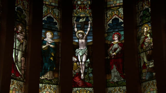A tableau of stained glass windows depicting the crucifixion of Jesus Christ.