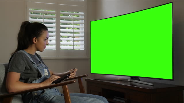 Tablet card pay, TV chromakey. Young woman.