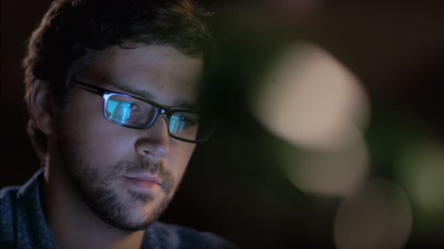 Tablet screen is reflected in man's glasses as he works late in office