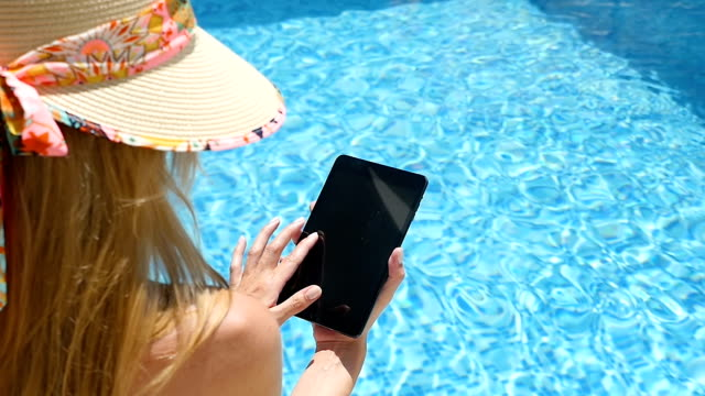 tablet & swimming pool - straw hat stock videos and b-roll footage
