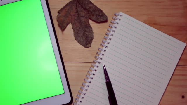tablet with green screen on old rustic table with notepad and notebook. - table top view stock videos & royalty-free footage