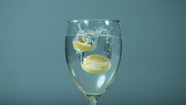 Tablets Falling and Dissolving into a Glass of Water against White Background, Slow Motion 4K