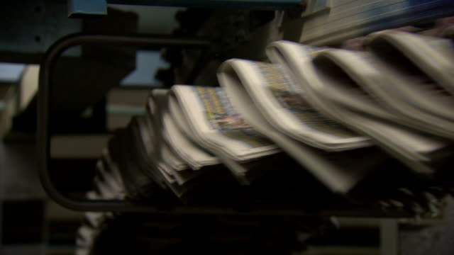 tabloid newspapers whir past on a printing press production line, uk. - journalism stock videos & royalty-free footage