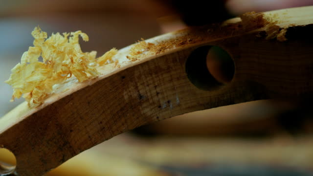 vidéos et rushes de tactile wood shavings and dust created when the sharp edges of a curved piece of wood are rounded are brushed away. - focus concept