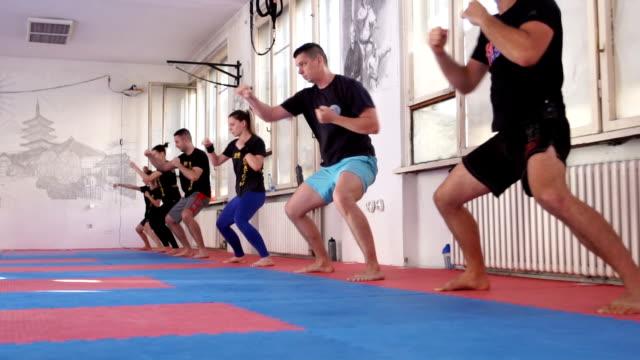 vidéos et rushes de classe d'yoga avec le grand groupe de personnes en slow motion - karaté