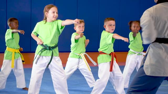 stockvideo's en b-roll-footage met taekwondo klasse oefenen stoten - driekwartlengte