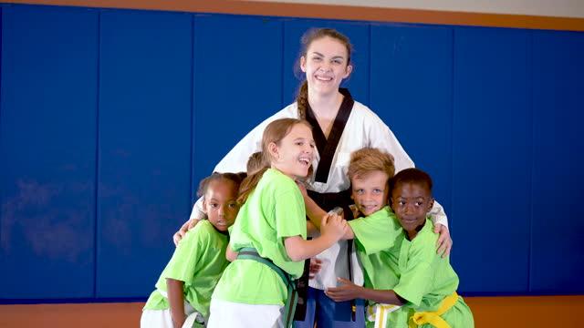 stockvideo's en b-roll-footage met taekwondo instructeur krijgt knuffel van haar studenten - 6 7 years