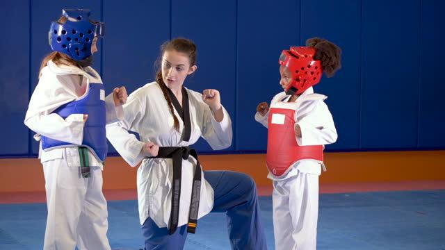 stockvideo's en b-roll-footage met taekwondo leraar met meisjes in beschermende kleding - 6 7 years