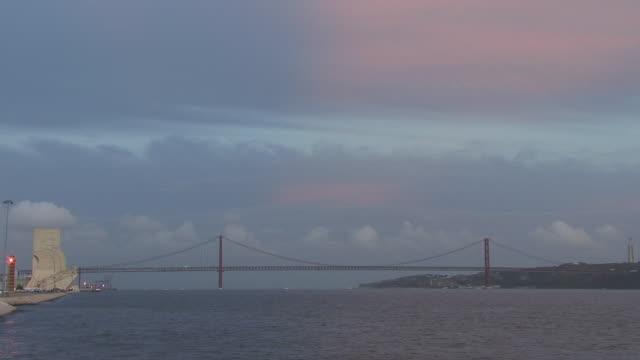ws tagus river flowing beneath april 25th bridge at dusk / lisbon, portugal - 4月25日橋点の映像素材/bロール