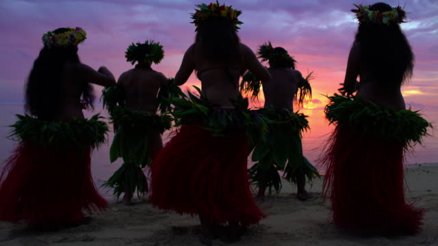 Tahitian males in warrior dress on sunset beach