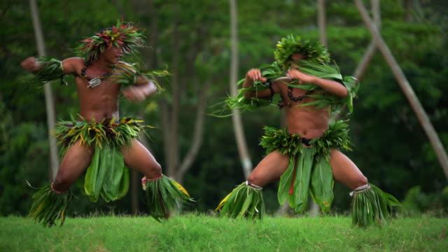 vidéos et rushes de tahitian males performing war dance in traditional costume - grâce