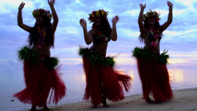 Tahitian Polynesian females dancing barefoot on sunset beach