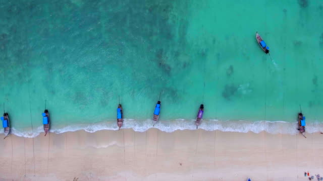 tail boats on tropical beach,aerial view - phi phi islands stock videos & royalty-free footage
