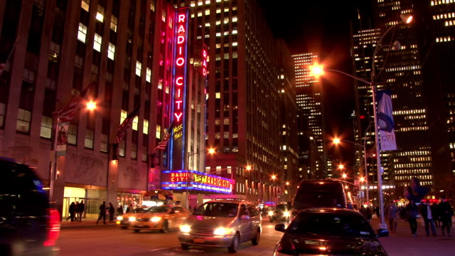 tail end rush hour traffic heading north on 6th avenue past radio city music hall in midtown manhattan - radio city music hall stock videos & royalty-free footage