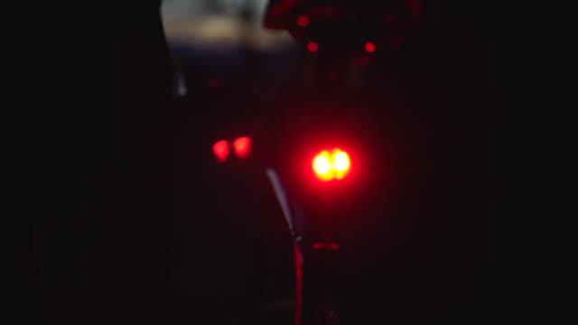 vidéos et rushes de lumière de queue d'un vélo avec le cycliste sur le point d'embarquer - traînée de lumière