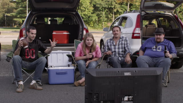 WS Tailgaters watching widescreen television and celebrating / Valhalla, New York, United States