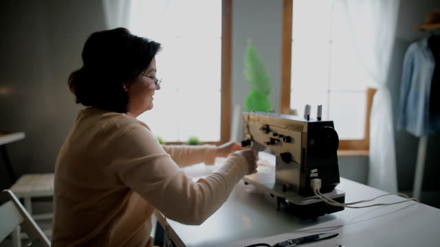 tailor at work on sewing machine in her tailor studio - sewing stock videos and b-roll footage