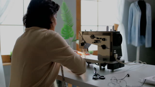 tailor at work on sewing machine in her tailor studio - sewing stock videos & royalty-free footage