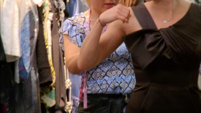 stockvideo's en b-roll-footage met ms tu tailor checking evening gown on model, new york city, new york, usa - avondjurk
