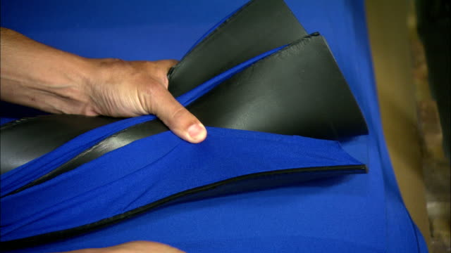 a tailor checks a bundle of neoprene fabric. - tailor stock videos & royalty-free footage