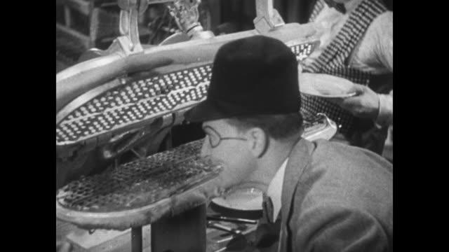 vídeos y material grabado en eventos de stock de 1934 tailor contentedly makes waffles on the pressing machine of a tailor shop - waffles