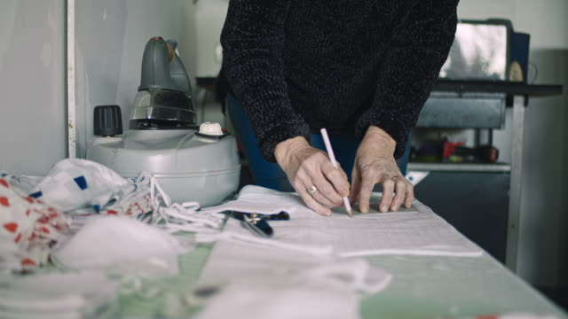 slo mo tailor cutting fabric to make homemade masks - charity and relief work stock videos & royalty-free footage