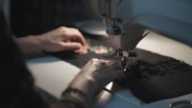 vidéos et rushes de textile de coupe de tailleur avec la machine à coudre pendant la nuit dans la lumière basse - atelier d'artisan