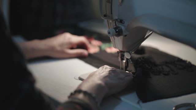 tailor cutting textile with sewing machine during the night in low light - cutting stock videos & royalty-free footage